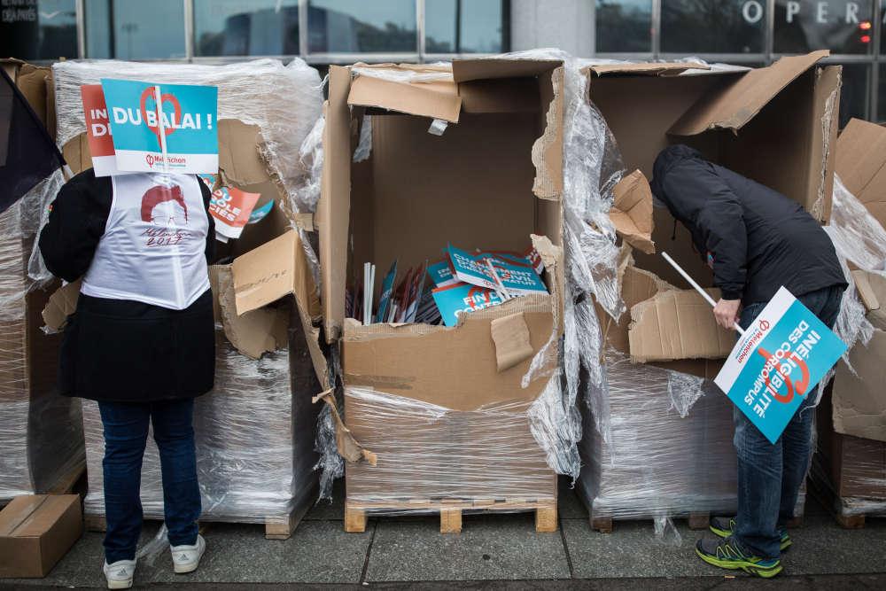 Devant l'Opéra Bastille, samedi 18 mars, drapeaux et pancartes sont distribués aux manifestants favorables à Jean-Luc Mélenchon.