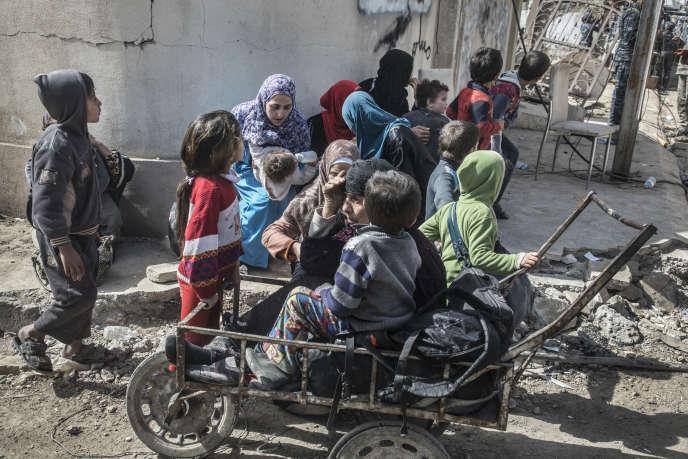 Des habitants du quartier Ghaslani fuient les combats dans Mossoul-Ouest, le 12 mars.