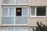 Un policier à la fenêtre de l'appartement, à Garges-lès-Gonesse (Val-d'Oise), de l'auteur de l'attaque d'Orly.