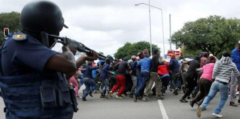 Un policier disperse une manifestation contre l'immigration clandestine à Pretoria, le 24 février 2017, en Afrique du Sud.