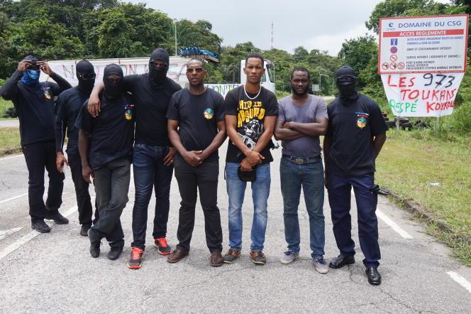 Des membres des 500 Frères et du collectif Toukans, devant le barrage qu'ils ont dressé sur la route menant au Centre spatial guyanais, à Kourou, mardi 22 mars.