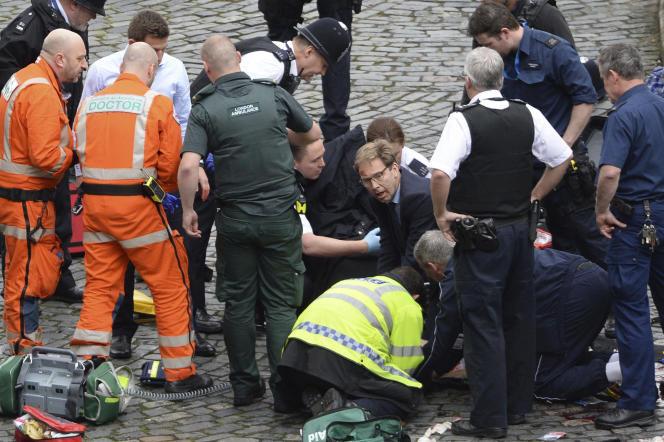 Le député Tobias Ellwood (au centre) est sorti du Parlement pour venir en aide, en vain, au policier blessé.