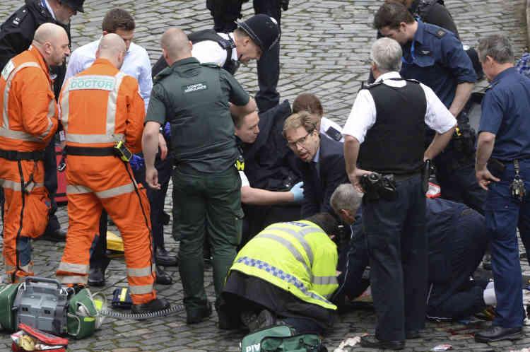 Le député Tobias Ellwood (au centre) est sorti du Parlement pour venir en aide, envain, au policier blessé.
