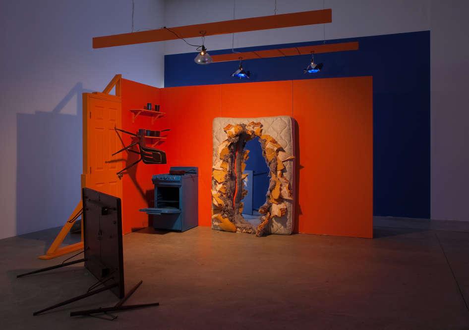 """«Les œuvres de Michele O'Marah sont inspirées de la culture cinématographique d'Hollywood et reprennent les clichés fabriqués par la machine à divertissement de la ville. Ses vidéos se concentrent sur des séries et films existants, recréés et transformés en des films à petit budget, souvent """"kitsch"""". L'installation """"Orange Set"""" ne présente qu'un fragment tiré de """"Barb Wire"""" (1996) avec Pamela Anderson. Ce décor est emprunté à la scène où Barb Wire utilise un matelas pour faire sauter le mur avant la fusillade qui se conclut par la fameuse réplique : """"Don't Call Me Babe"""".»"""