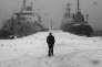 Tempête de neige dans le port de Mourmansk, sur la mer de Barents, en Russie. Oleg KLIMOV/PANOSA man walks through the snow with ships visible in the distance in the port city of Murmansk on the Barent Sea. *** Local Caption *** Europe, Shipping, Industry, Snow,
