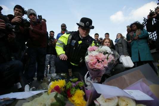 Un« bobby» rend hommage aux victimes de l'attaque à proximité du Parlement britannique, à Londres, le 23 mars.