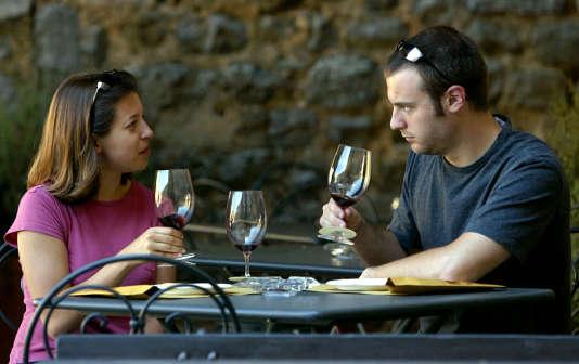 Un couple goût verres de Brunello di Montalcino vin dans la ville toscane de Montalcino dans le centre de l'Italie.