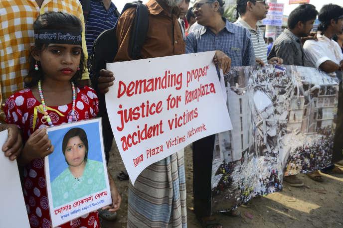 Une jeune fille bangladaise tient une photo de sa mère morte lorsque l'usine de textile du Rana Plaza s'est effondrée, le 26 avril 2013 dans la banlieue de Dacca, la capitale du Bangladesh. Plus d'un millier d'ouvriers y ont trouvé la mort.
