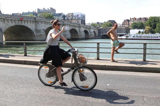 Un femme sur un velib, le 20 juillet à Paris.