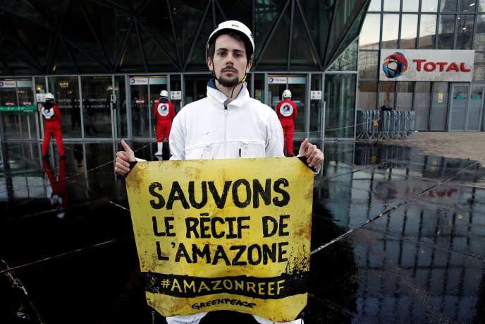 Un militant de l'ONG écologiste Greenpeace manifeste à la Défense devant le siège de la société Total, en mars 2017.
