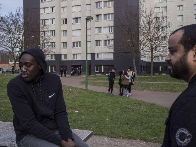 A Aulnay-sous-Bois (Seine-Saint-Denis), fin février. Des anciens du quartier discutent avec quelques jeunes. Au loin, une opération de la BAC dans un hall.