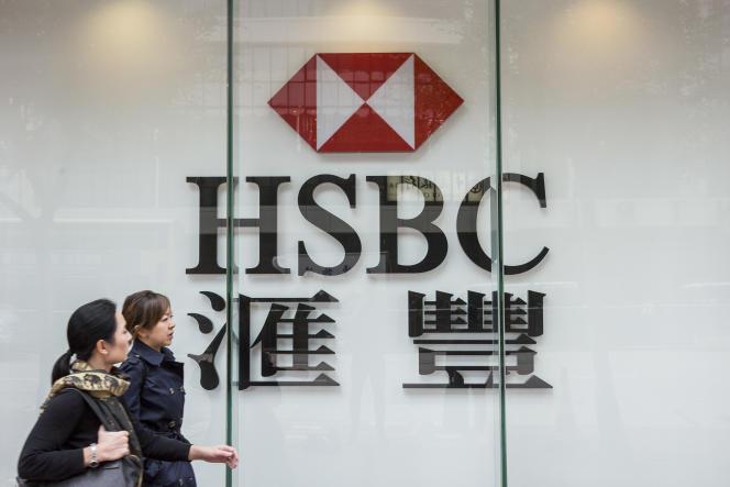 Deux femmes marchent devant HSBC, le 21 février à Hongkong.