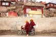Dans le camp de Yarchen Gar, le 18 février 2017, des moines passent devant les habitations rudimentaires.