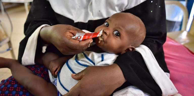Une femme nourrit son enfant souffrant de malnutrition avec un sachet de Plumpy'Nut, le 14 juin 2016, au Niger.