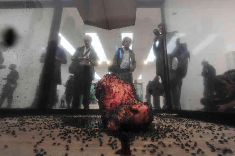 En 1990, Damien Hirst réalise son œuvre la plus saisissante à ce jour, «A Thousand Years ». Dans une immense boîte en verre, les mouches volettent vers une mort programmée : grillées sur un tue-mouches électrique ou noyées dans le sang d'une tête de vache gisant au sol. Ici à la Tate Modern à Londres, le 2 avril 2012.
