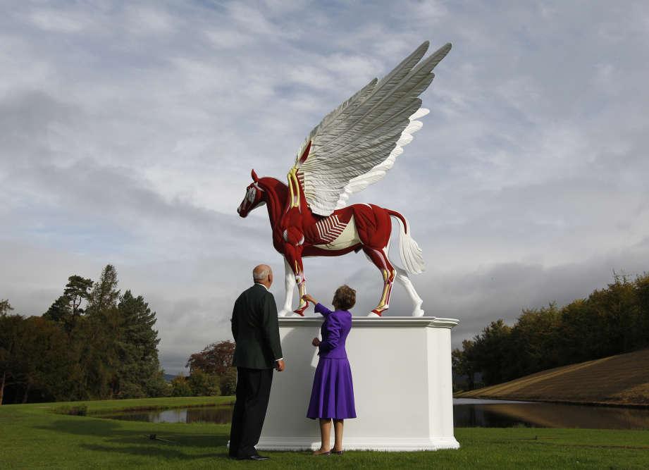 L'une des stars vivantes de l'art contemporain occupera, à partir du 9 avril, le Palazzo Grassi et la Pointe de la Douane, à Venise. Retour sur les œuvres marquantes de l'artiste britannique fasciné par la mort. Ici, le duc et la duchesse de Devonshire devant une sculpture de Damien Hirst, dans les jardins de leur maison de Chatsworth en Angleterre, en septembre 2011.