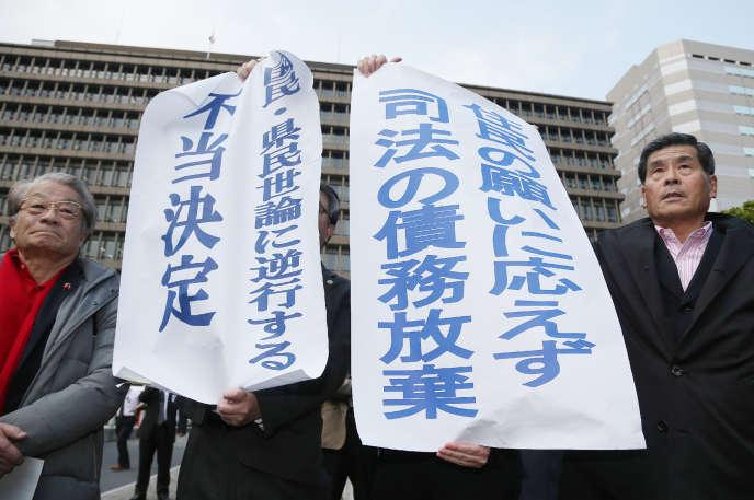 Les plaignants ont fustigé «une décision injuste ignorant l'opinion publique», selon cette affiche brandie devant la Haute cour d'Osaka (Japon) le 28 mars 2017