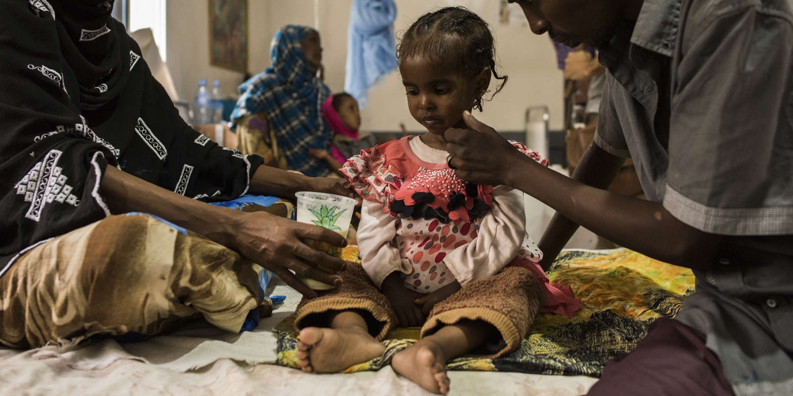 SOMALIA. Somaliland. Borama. March 21, 2017. Dagan Qaalib, 4, sits with her mother and father at the malnutrition clinic in Borama hospital. She was admitted to the hospital at weight of 7.1 kilograms and is suffering from severe acute malnutrition. Somalia is on the edge of famine as drought conditions have left 6 million people in need of food aid throughout the country.