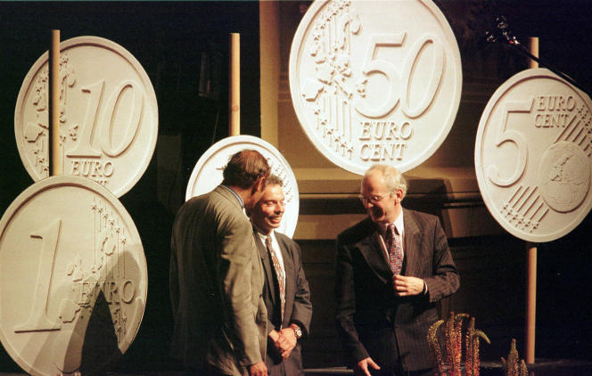 June 16, 1997, Belgian designer Luc Luycx is surrounded by the new Euro coins he designed during a presentation in Amsterdam. At left is European financial affairs commissioner Yves-Thibauld De Silguy, right, Dutch Finance Minister Gerrit Zalm. (AP Photo/Jerome Delay, File).