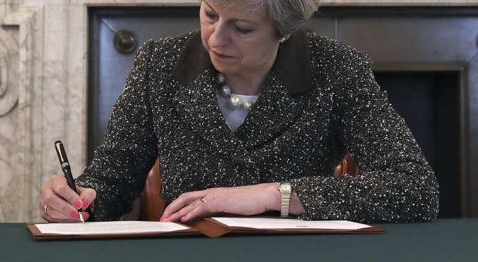 Theresa May signe la lettre par laquelle elle demande au président du Conseil européen la sortie du Royaume-Uni de l'Union européenne, à Londres, le 28 mars.