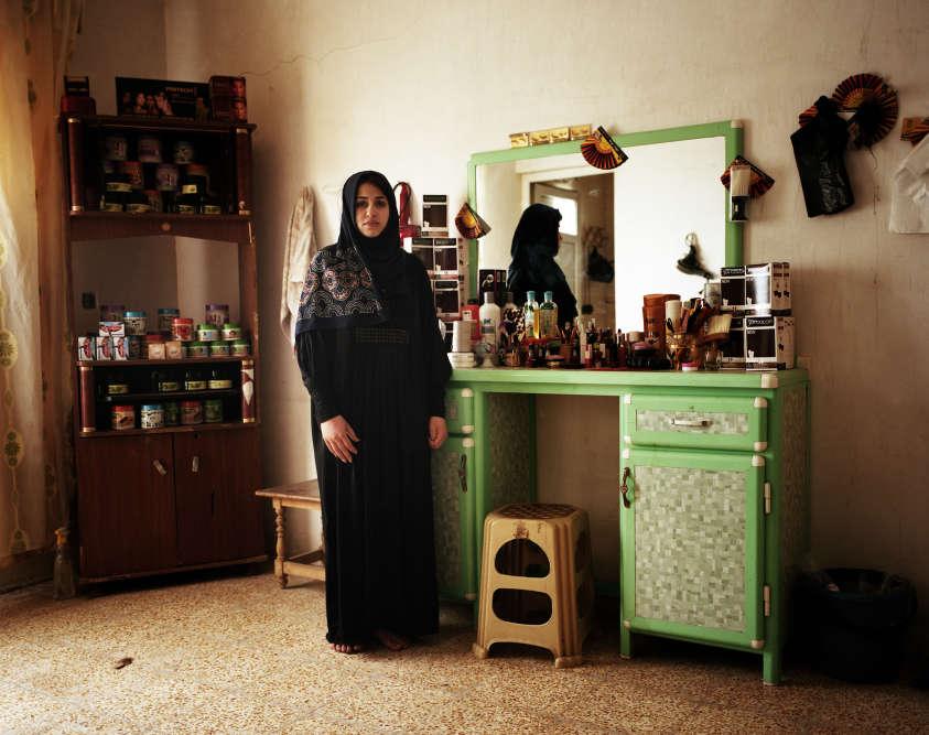 Ihem, 16ans, pose dans le salon de beauté tenu par sa famille. Après deux ans d'interdiction d'exercer par l'organisation Etat islamique (EI), le salon vient de rouvrir.