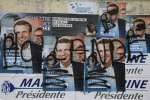 A graffiti with the name of French President Francois Hollande is seen on campaign posters of Emmanuel Macron, head of the political movement En Marche ! (or Onwards !) and candidate for the 2017 presidential election, in Villers-Cotterets, France, March 17, 2017. REUTERS/Pascal Rossignol
