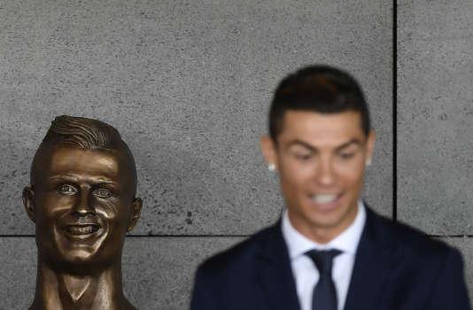 Cristiano Ronaldo et la statue à son effigie, à l'aéroport de Madère, le29mars.