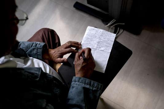 Un traducteur prend des notes pour retranscrire les réponses de Merhawi à Fontenay-sous-Bois, le 28 mars 2017.