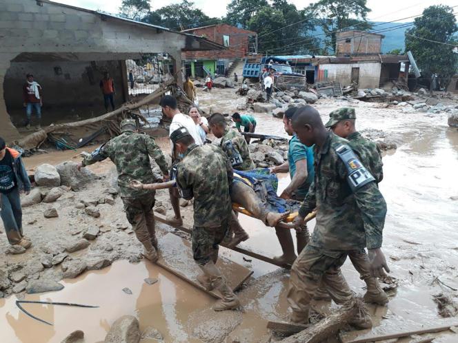Des soldats de l'armée colombienne portent secours à des habitants de Mocoa, ville frappée par des coulées de boue mortelles, dans la nuit de vendredi à samedi.