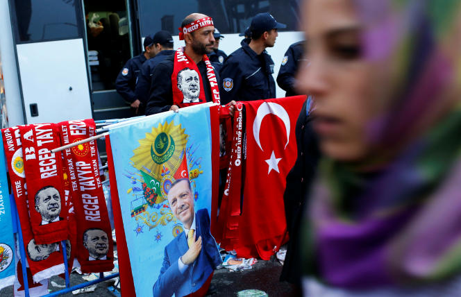Un vendeur de rue propose écharpes et drapeaux à l'effigie du président turc, Recep Tayyip Erdogan, à l'occasion de sa venue pour un meeting, à Diyarbakir, une ville majoritairement kurde située dans l'ouest du pays, samedi 1er avril.