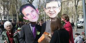 Protesters wearing masks depicting the two French presidential election candidates, respectively left and far left, Benoit Hamon and Jean-Luc Melenchon (R), take part in a fake mariage after a bullish Melenchon rebuffed a desperate appeal by Hamon for the two to join forces on March 30, during a demonstration calling for a joint candidacy in Paris on April 1, 2017.  / AFP / Zakaria ABDELKAFI