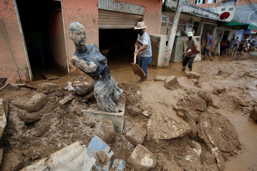 Dans les rues de la ville, les habitants nettoient la boue et les matériaux divers chariés par la coulée.
