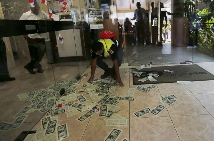 Un syndicaliste ramasse des prospectus ayant l'apparence de billets de banquedans le hall d'entrée deMossack Fonseca lors d'une manifestation à Panama City le 13 avril 2016.