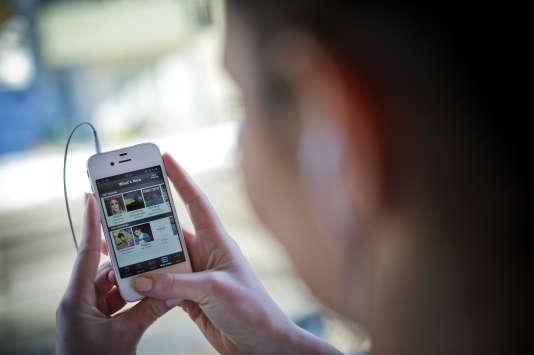 Une femme utilisant Spotify sur son smartphone, le 7 mars, à Stockholm.