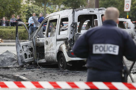 Un policier devant le véhicule de police incendié à Viry-Châtillon, le 8 octobre.