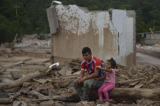 Un homme et sa fille se tiennent au milieu des dégâts causés par la coulée de boue à Mocoa, en Colombie, le 4 avril.
