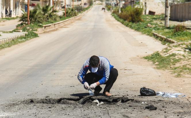 Un homme récupère des échantillons à l'endroit où le missile a explosé.