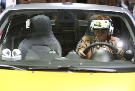 Une femme utilise un casque de réalité virtuelle à l'intérieur d'une voiture intelligente. Berlin, Allemagne, 6 avril, 2016.