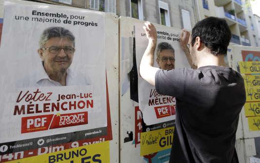 Un partisan de Jean-Luc Mélenchon colle une affiche, le 6 avril à Marseille.