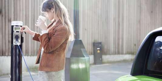 Jeune femme rechargeant sa voiture électrique.
