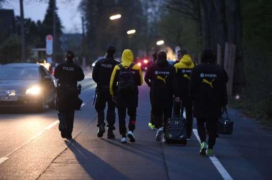 Des membres de l'équipe de Dortmund escortés par la police après l'évacuation de leur bus, mardi 11 avril.