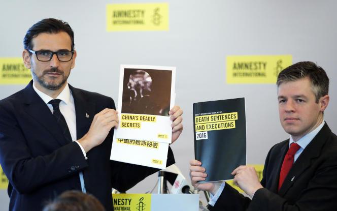 Le directeur d'Amnesty International pour l'Asie de l'Est, Nicholas Bequelin (à gauche), et James Lynch, directeur adjoint de l'ONG, exhibent des copies du rapport annuel sur la peine de mort lors d'une conférence de presse à Hongkong, le 10 avril 2017.