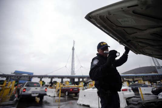 Un agent américain contrôle une voiture à la frontière entre les Etats-Unis et le Mexique.