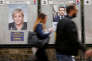 People walk past campaign posters of Marine Le Pen (L), French National Front (FN) political party leader, and Emmanuel Macron (R), head of the political movement En Marche! (Onwards!), two of the eleven candidates who run in the 2017 French presidential election in Paris, France, April 10, 2017. REUTERS/Gonzalo Fuentes