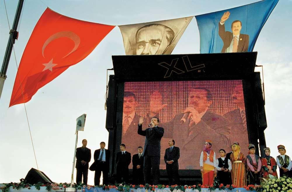 Sur cette photo prise à Istanbul en octobre 2002, Recep Tayyip Erdogan, leader du Parti de la justice et du développement (AKP) qu'il a fondé un an plus tôt, est en campagne. Il deviendra premier ministre quelques mois plus tard. Au-dessus de l'estrade, entre son portrait et le drapeau turc, flotte au vent la figure de Mustafa Kemal Atatürk, fondateur de la Turquie moderne, dont il fut le premier président de la Républiquede 1923 à 1938. Quinze ans après ce cliché, Erdogan, devenu président à son tour, s'apprête, s'il remporte le référendum du 16avril, à modifier la Constitution. Ses opposants, qui dénoncent depuis longtemps son entreprise de déconstruction de la République laïque fondée par Atatürk, s'inquiètent cette fois-ci d'une révision constitutionnelle, qui prévoit le renforcement du pouvoir présidentiel en supprimant notamment le poste de premier ministre.