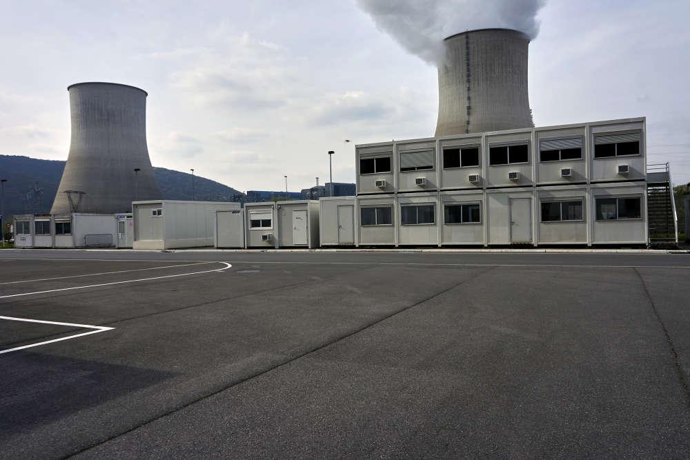 La centrale nucléaire de Chooz B (ici, le 5 avril), dans les Ardennes, compte deux réacteurs de 1 450 mégawatts (MW), couplés au réseau en1996 et 1997, dont les tours de refroidissement sont plantées dans une boucle de la Meuse. Le même site abrite aussi, dans des cavernes souterraines, le premier réacteur à eau pressurisée français, ChoozA, de 305 MW. Mis en service en 1967, il a été arrêté en 1991. Au premier plan, des bâtiments préfabriqués abritent les services de la déconstruction de cette unité.
