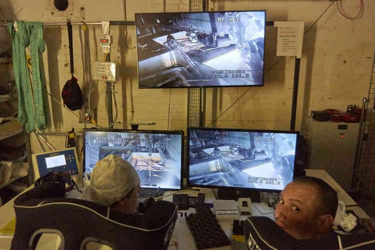 Dans la cavernes des équipements auxiliaires, deux employés commandent, à distance, le robot Predator, dont les pinces et les scies découpent les tôles et les bidons contenant des résines et des effluents contaminés.