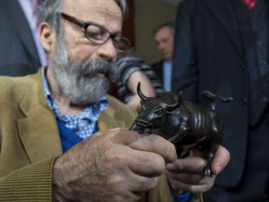 Le sculpteur Arturo Di Modica tient un modèle du« Charging Bull» lors de sa conférence de presse, le 12avril 2017, à New York.