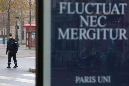 Un policier derrière un panneau d'informationde la Ville de Paris rendant hommage aux victimes du 13novembre.