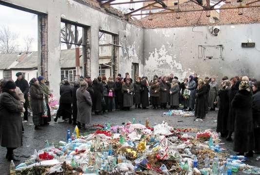 Des rescapés et des proches des victimes se recueillent dans les décombres de l'école de Beslan, le 3 mars 2005. (FILES)
